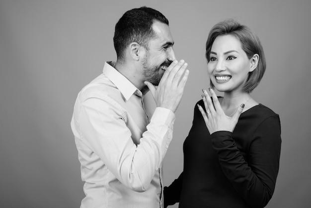 Porträt eines multiethnischen paares zusammen und verliebt auf grau in schwarzweiß