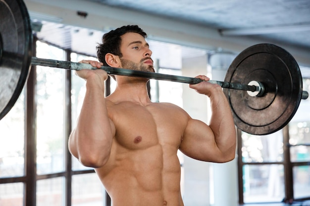 Porträt eines muskulösen mannes, der mit langhantel im fitnessstudio trainiert