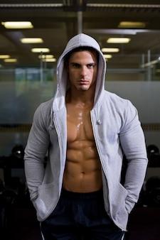 Porträt eines muskulösen mannes in der haubenjacke an der turnhalle