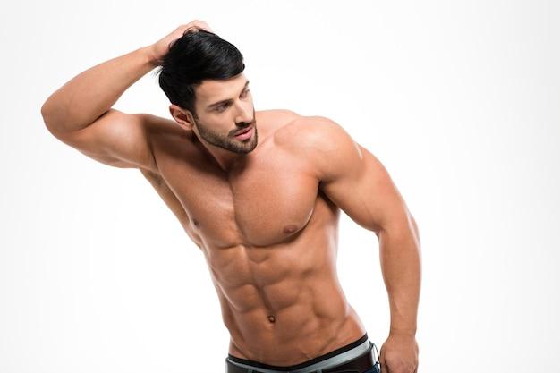 Porträt eines muskulösen mannes mit nacktem oberkörper, der lokal auf einer weißen wand aufwirft