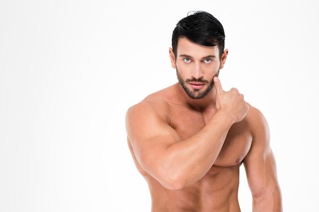 Porträt eines muskulösen nackten mannes, der front lokalisiert auf einer weißen wand betrachtet