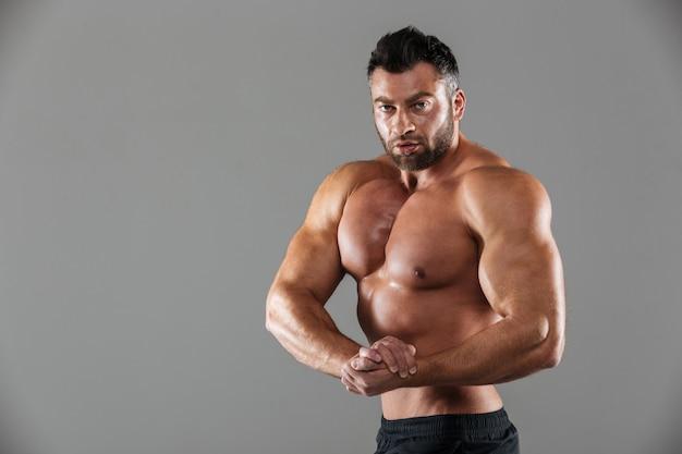 Porträt eines muskulösen überzeugten hemdlosen männlichen bodybuilders