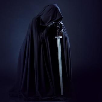 Porträt eines mutigen kriegerwanderers in einem schwarzen umhang und schwert in der hand.