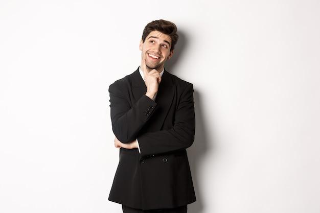 Porträt eines nachdenklich lächelnden mannes in stilvollem partyanzug, der die obere linke ecke betrachtet und denkt, dinge abbildet und auf weißem hintergrund steht.