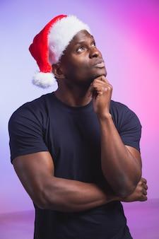 Porträt eines nachdenklichen afroamerikanischen mannes in weihnachtsmütze und lässigem t-shirt auf buntem hintergrund