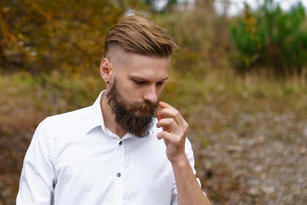 Porträt eines nachdenklichen, bärtigen, attraktiven jungen mannes im weißen hemd mit blick auf einen herbstpark im oktober...