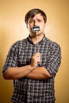 Porträt eines nachdenklichen hipster-typs, der mit falschem schnurrbart am stock posiert