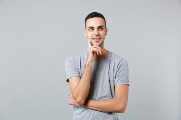 Porträt eines nachdenklichen jungen mannes in freizeitkleidung, der beiseite schaut und handstütze auf das kinn legt