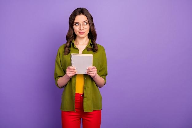 Porträt eines nachdenklichen mädchens hipster halten notizbuch denken gedanken entscheiden thema tagebuch projekt tragen stil stilvolle modische rote hosen hosen isoliert violetter farbhintergrund