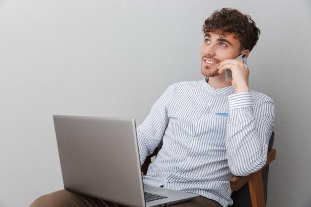 Porträt eines nachdenklichen mannes im hemd, der auf dem smartphone spricht und einen silbernen laptop benutzt, während er auf einem stuhl sitzt, isoliert über grauer wand?