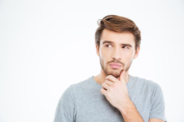 Porträt eines nachdenklichen zufälligen mannes, der isoliert auf weißem hintergrund steht