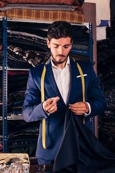 Porträt eines nähenden gewebes des männlichen modedesigners mit nadel