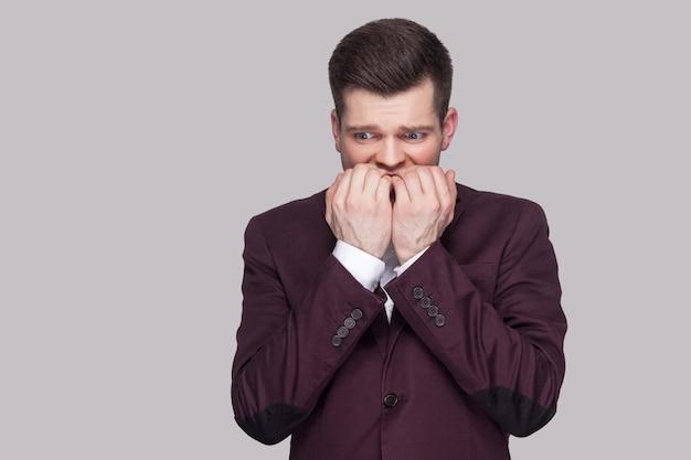 Porträt eines nervösen, gutaussehenden jungen mannes in violettem anzug und weißem hemd, der steht, wegschaut und nägel mit sorgengesicht beißt. indoor-studioaufnahme, auf grauem hintergrund isoliert.