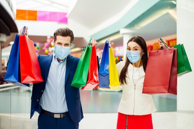 Porträt eines netten, attraktiven, gesunden, stilvollen, trendigen ehepaares mit gaze-maske, das neue dinge trägt, die das einkaufszentrum an öffentlichen plätzen besuchen und spaß in der sozialen distanz haben