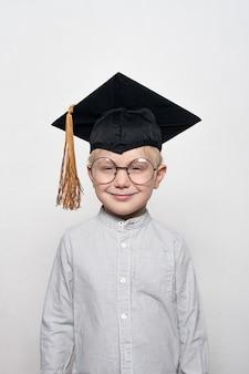 Porträt eines netten blonden jungen in den großen gläsern und in einem akademischen hut.