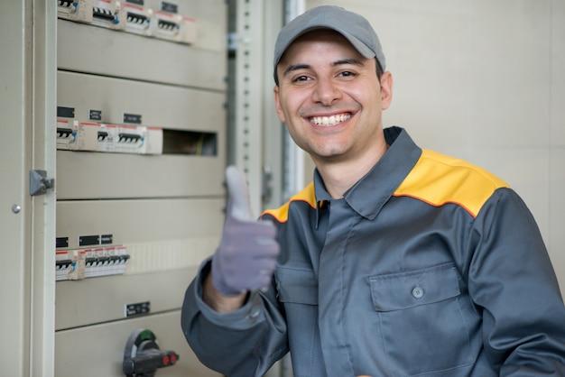 Porträt eines netten elektrikers, der daumen aufgibt