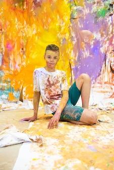 Porträt eines netten glücklichen jungen, der spaß malt und hat