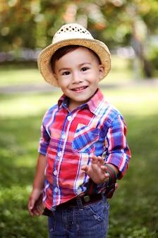 Porträt eines netten glücklichen kindes in einem strohhut, der in einem sommerpark spielt.