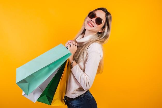 Porträt eines netten glücklichen mädchens mit einkaufstaschen.