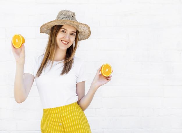 Porträt eines netten jungen mädchens im hut, der zwei scheiben orange auf weißer wand hält