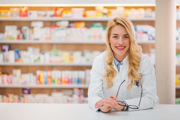 Porträt eines netten jungen weiblichen apothekers, der auf einem zähler am drogeriemarkt, kamera betrachtend sich lehnt.