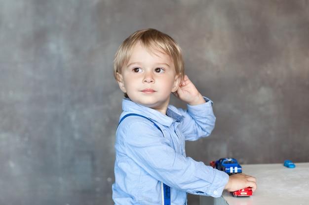 Porträt eines netten kleinen jungen, der mit bunten spielzeugautos spielt. aktiver junge spielt mit spielzeugautos im kindergarten. das konzept der kindheit und der kindlichen entwicklung. kind zu hause im kinderzimmer. baby zu hause