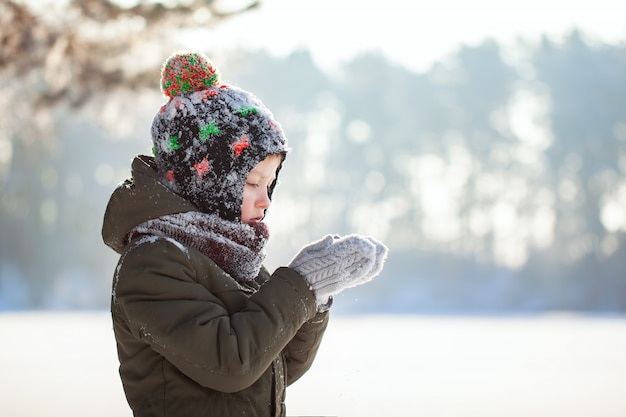 Porträt eines netten kleinen jungen in der warmen kleidung, die draußen auf schnee während der schneefälle am sonnigen tag des winters durchbrennt.