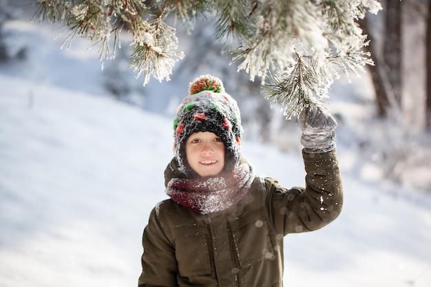 Porträt eines netten kleinen jungen in der warmen kleidung, die draußen während der schneefälle am sonnigen tag des winters spielt.