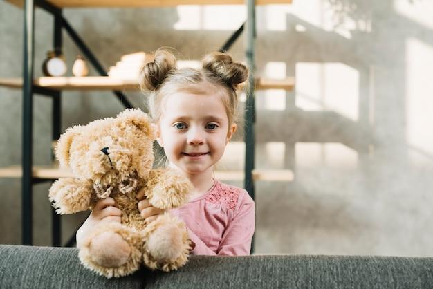 Porträt eines netten kleinen mädchens, das mit teddybären steht