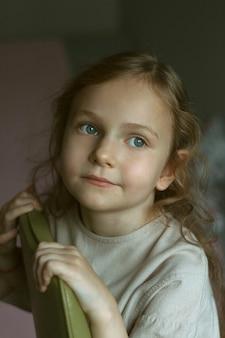 Porträt eines netten kleinen mädchens mit dem gelockten haar, das auf einem grünen stuhl in einem raum in einem hellen kleid sitzt