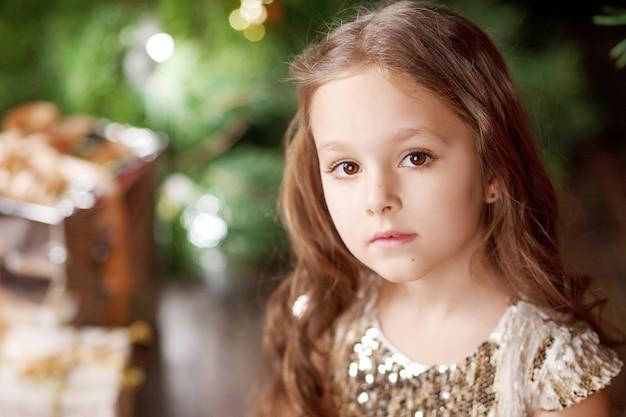 Porträt eines netten langhaarigen kleinen mädchens in den kleiderweihnachtslichtern. weihnachts- und neujahrsfeier.