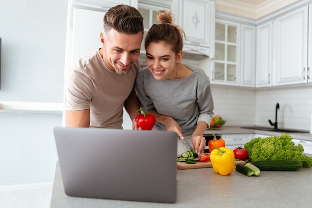 Porträt eines netten liebevollen paares, das zusammen salat kocht
