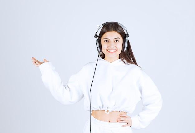Porträt eines netten modells des jungen mädchens, das mit kopfhörern steht.