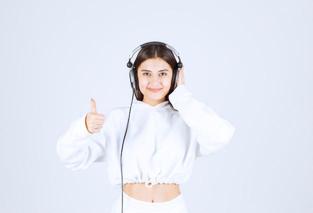 Porträt eines netten modells des jungen mädchens mit den kopfhörern, die einen daumen oben zeigen.
