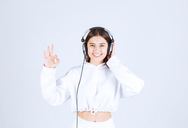 Porträt eines netten modells des jungen mädchens mit kopfhörern, die stilles zeichen zeigen.