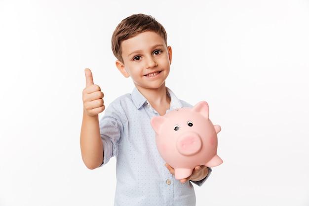 Porträt eines netten niedlichen kleinen kindes, das sparschwein hält