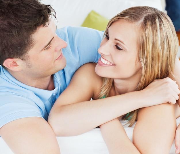 Porträt eines netten paares, das einander sich entspannt auf dem sofa betrachtet
