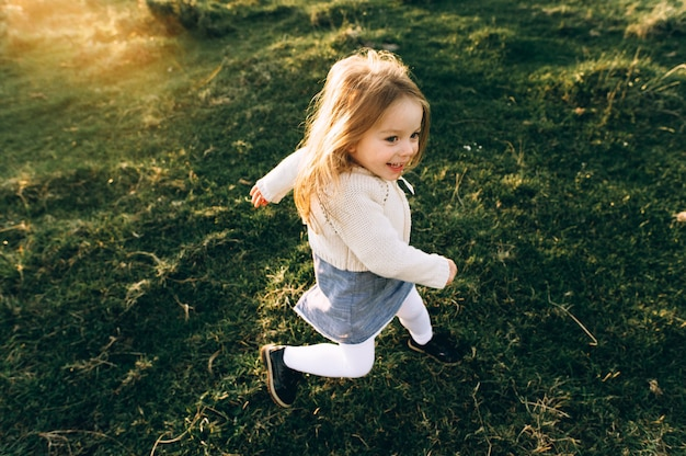 Porträt eines netten schönen und glücklichen mädchens, das durch das sonnige feld läuft