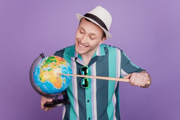 Porträt eines neugierigen, charmanten touristen, der den globus hält, zeigt zeiger-look afrika auf violettem hintergrund an