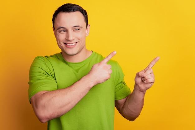 Porträt eines neugierigen fördernden kerls, der auf gelbem hintergrund eine leere stelle mit dem finger zeigt