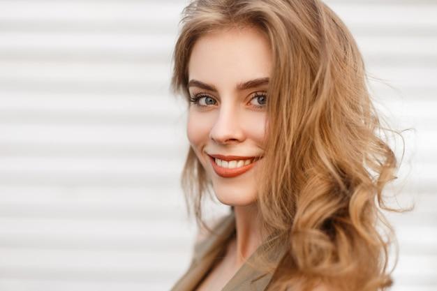 Porträt eines niedlichen charmanten mädchens mit einem wunderbaren lächeln mit natürlichem make-up mit lockigem haar mit blauen augen auf einer weißen wand. glückliche positive junge frau. nahansicht.