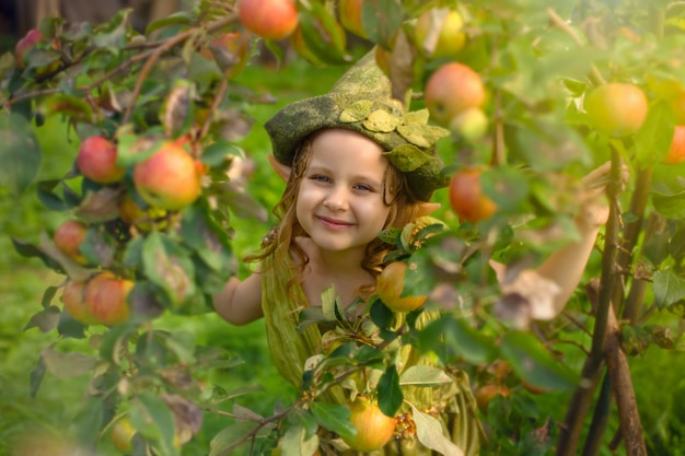Porträt eines niedlichen hübschen mädchens in einem grünen gnomenhut in einem baum mit äpfeln.