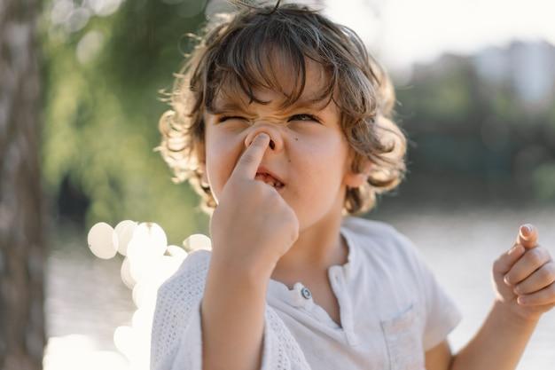 Porträt eines niedlichen jungen, der in der natur nahe dem fluss spielt.