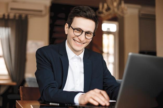 Porträt eines niedlichen jungen geschäftsmannes, der an seinem laptop sitzt, während in einem coffeeshop die kamera lächelnd betrachtet.