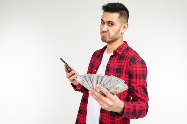 Porträt eines niedlichen kerls mit einem haufen geld, der am telefon auf einem weißen studio mit kopierraum spricht