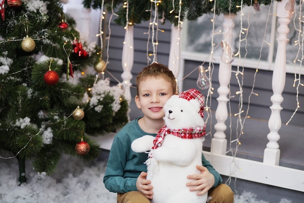 Porträt eines niedlichen kleinen jungen, der einen weichen teddybär umarmt