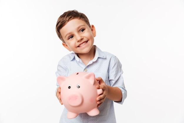 Porträt eines niedlichen kleinen kindes der kirsche, das sparschwein hält