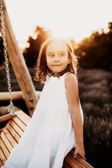 Porträt eines niedlichen kleinen mädchens, das auf einer hölzernen schaukel sitzt und weg lächelt gegen sonnenuntergang gekleidet im weißen kleid.