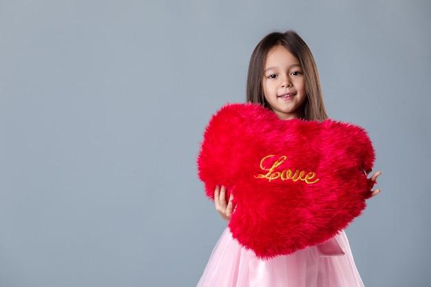 Porträt eines niedlichen kleinen mädchens im rosa kleid, das großes rotes herz umarmt