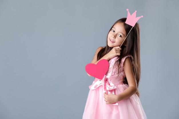 Porträt eines niedlichen kleinen mädchens im rosa kleid, das papierherz und prinzessin krone hält